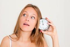 Frauenholdingalarmuhr Lizenzfreie Stockbilder