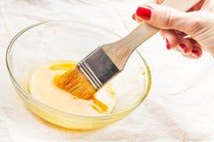 Frauenholdingbürste tauchte in gewischtes Ei ein Stockbild