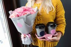 Frauenholdingbehälter für Kaffee zum Mitnehmen und Blumen lizenzfreie stockbilder
