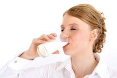 Frauenholdingglas Milch im Bett auf weißem Hintergrund Stockfotografie