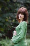 Frauenholdinghände auf ihrem schwangeren Bauch Lizenzfreies Stockfoto