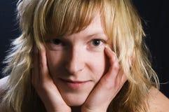 Frauenholdinghände zum Gesicht Stockfotografie