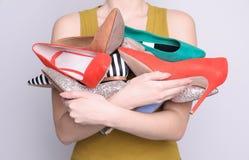Frauenholdinghaufen von eleganten Schuhen auf hellem Hintergrund lizenzfreie stockfotos