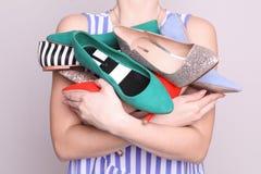 Frauenholdinghaufen von eleganten Schuhen auf hellem Hintergrund stockfotografie