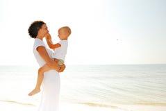 Frauenholdingjunge auf Strand Lizenzfreie Stockfotos