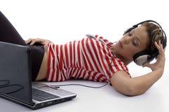 Frauenholdingkopfhörer und Betrachten des Laptops Stockbild