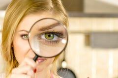 Frauenholdinglupe nah an Auge stockfotografie