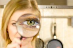 Frauenholdinglupe nah an Auge lizenzfreie stockfotografie