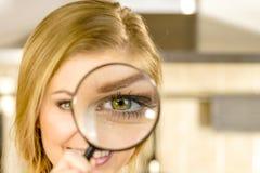 Frauenholdinglupe nah an Auge lizenzfreies stockfoto