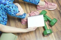 Frauenholdingnotizbuch mit Zeitplan ihrer persönlichen Praxis Aktiver Lebensstil täglich stockfotos