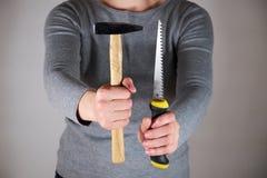 Frauenholdingsäge und -hammer Lizenzfreie Stockfotos