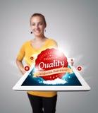 Frauenholdingtablette mit rotem Qualitätskennsatz Stockbild