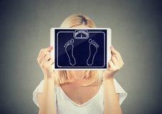 Frauenholdingtabletten-Gewichtsskala vor ihrem Gesicht stockbilder