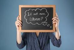 Frauenholdingtafel mit Phrase wenn nicht jetzt Wann? auf Farbhintergrund Schmutz-Hintergrund f?r Ihre Ver?ffentlichungen lizenzfreies stockbild