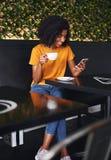 Frauenholdingtasse kaffee unter Verwendung des Handys im Café stockfotografie