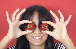 Frauenholdingtomate über Augen Stockbilder