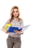 Fraueningenieur, der auf Dateien schaut und einen Sturzhelm hält Lizenzfreies Stockfoto