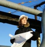 Fraueningenieur gegen Rohrleitungen mit Zeichnungen Stockfotos