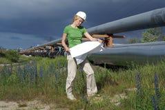Fraueningenieur mit weißen Sicherheitshutzeichnungen Stockbild