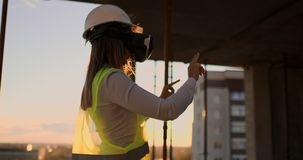 Fraueningenieurerbauer auf dem Dach des Gebäudes auf Sonnenuntergangständen in VR-Gläsern und -bewegungen seine Hände unter Verwe stock footage