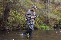 Frauenjäger, der kleinen Fluss im Wald kreuzt stockbild