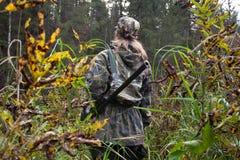 Frauenjäger mit Gewehr auf dem Flussufer Lizenzfreies Stockfoto