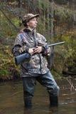 Frauenjäger mit Gewehr auf kleinem Fluss im Wald Stockfoto