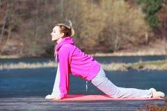 Frauenjugendliche im Trainingsnazug, der Übung auf dem Pier im Freien tut stockbilder