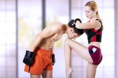 Frauenkämpfer, der in der Hand Knie tritt Lizenzfreie Stockfotografie