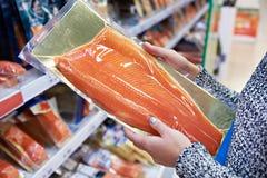 Frauenkäufe in gesalzenen Lachsen des Supermarktes lizenzfreie stockfotos
