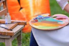 Frauenkünstler ` s Hand drückte von den Rohren zusammen, das Ölfarbe auf hölzernem erblassen Lizenzfreies Stockfoto