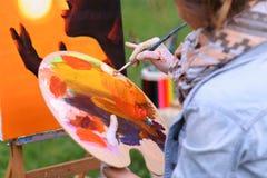 Frauenkünstler ` s Hand drückte von den Rohren zusammen, das Ölfarbe auf hölzernem erblassen Stockfoto
