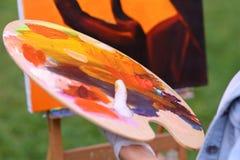 Frauenkünstler ` s Hand drückte von den Rohren zusammen, das Ölfarbe auf hölzernem erblassen Lizenzfreie Stockfotos
