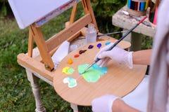 Frauenkünstler ` s Hand drückte von den Rohren zusammen, das Ölfarbe auf hölzernem erblassen Lizenzfreies Stockbild