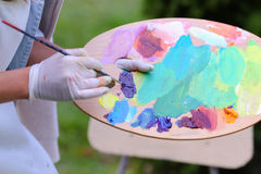 Frauenkünstler ` s Hand drückte von den Rohren zusammen, das Ölfarbe auf hölzernem erblassen Stockfotos