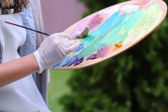 Frauenkünstler ` s Hand drückte von den Rohren zusammen, das Ölfarbe auf hölzernem erblassen Stockbild