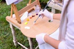 Frauenkünstler ` s Hand drückte von den Rohren zusammen, das Ölfarbe auf hölzernem erblassen Lizenzfreie Stockfotografie