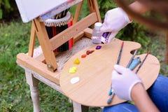 Frauenkünstler ` s Hand drückte von den Rohren zusammen, das Ölfarbe auf hölzernem erblassen Stockfotografie