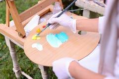 Frauenkünstler ` s Hand drückte von den Rohren zusammen, das Ölfarbe auf hölzernem erblassen Lizenzfreie Stockbilder