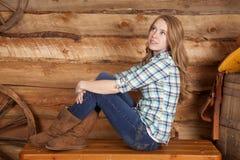 Frauenkariertes hemd sitzen Seitenbeine herauf Holz stockfoto