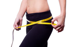 Frauenkarosseriensorgfalt und gelbes Maß auf Schenkeln Stockfoto