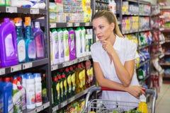 Frauenkaufprodukte mit ihrer Laufkatze Lizenzfreie Stockbilder