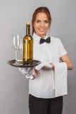 Frauenkellnerin mit einer Flasche des Weins und des Weinglases Lizenzfreie Stockbilder
