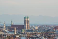 Frauenkirche e centro urbano di Monaco di Baviera, Germania con le alpi dentro Immagine Stock