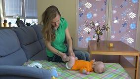Frauenkleiderbaby mit orange Farbkörperstoff auf Sofa 4K stock video