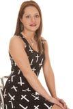 Frauenkleiderkreuze sitzen kleines Lächeln stockfotografie