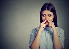 Frauenklemmnase mit Fingerblicken mit dem sideway Ekel etwas stinkt schlechten Geruch stockfoto