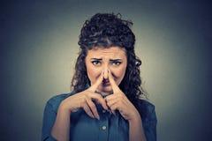 Frauenklemmnase mit Fingerblicken mit Ekel etwas stinkt schlechten Geruch lizenzfreie stockbilder