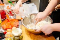 Frauenkoch, der Teig in der Schüssel zubereitet Lizenzfreie Stockfotos