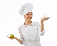 Frauenkoch wählt zwischen einem Apfel und einem Kuchen Lizenzfreies Stockfoto